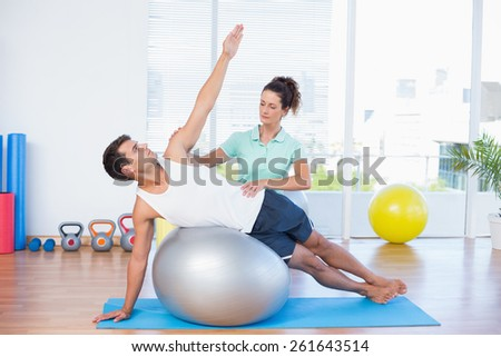Trainer helping man with exercise ball in fitness studio - stock photo