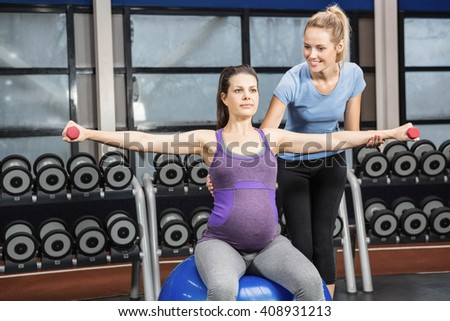 Trainer helping pregnant woman at the gym with dumbbell