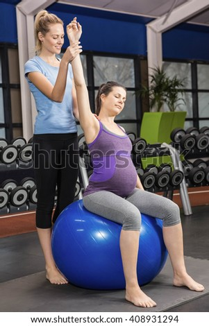 Trainer helping pregnant woman exercising on an exercise ball at the gym - stock photo