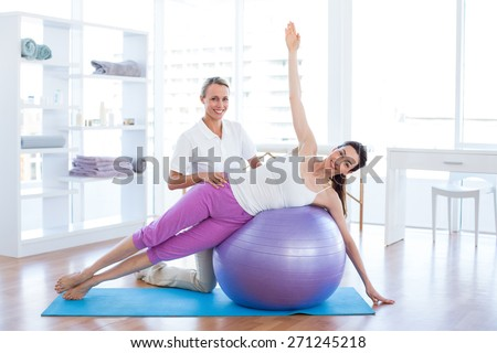 Trainer helping woman on exercise ball in medical office - stock photo