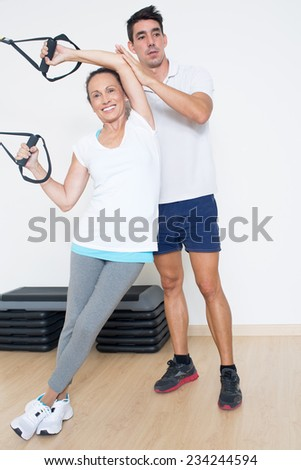 Trainer helps elderly woman with fitness exercise