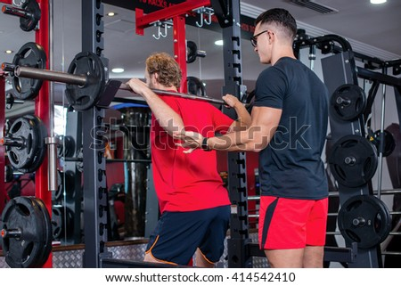 Trainer helps to train in the gym. Support in the sport. Confident athletic trainer support the barbell with a load in the gym. - stock photo