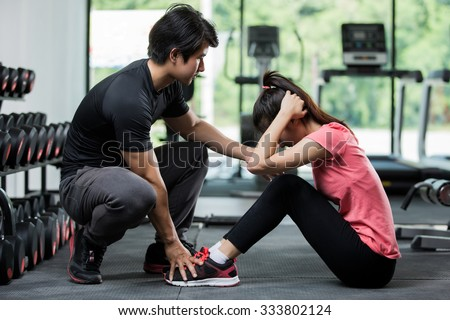 Trainer holding a woman in the leg exercise by Sit-up - stock photo