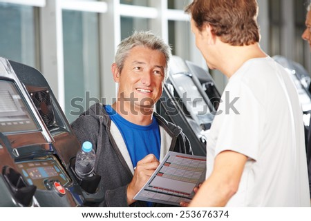 Trainer in fitness center advising senior man on a treadmill - stock photo