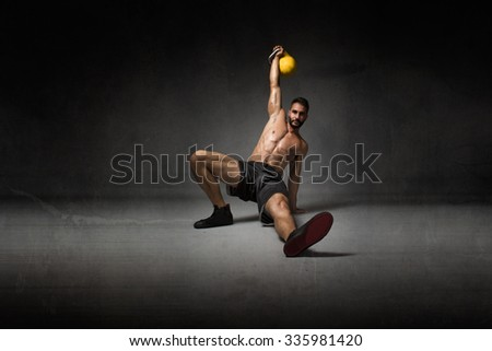 trainer lying down with kettlebell on hand, dark background - stock photo