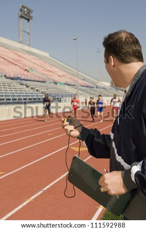 Trainer measuring time while athletes racing - stock photo