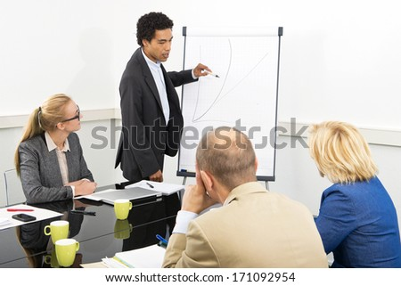 trainer provides explanation of an in-company workshop, standing next to a graph, drawin on a flip over - stock photo