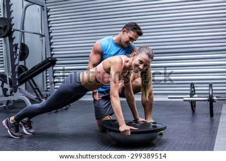Trainer supervising a muscular woman doing bosu ball exercises - stock photo