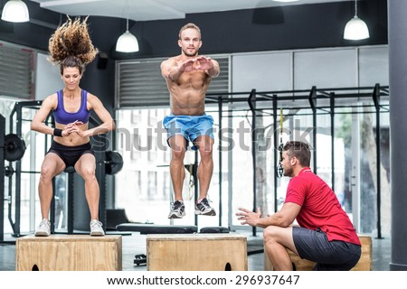 Trainer supervising muscular athletes doing jumping squats