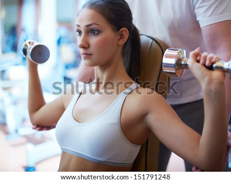Trainer supporting a fit girl exercising with dumbbells - stock photo