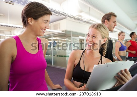 Trainer talking to her client on the treadmill at the gym - stock photo