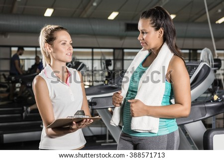 Trainer talking with woman at the gym