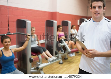 Trainer teaching women in weights room in gym - stock photo