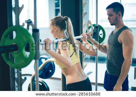 Trainer teaching young woman how to lift weight