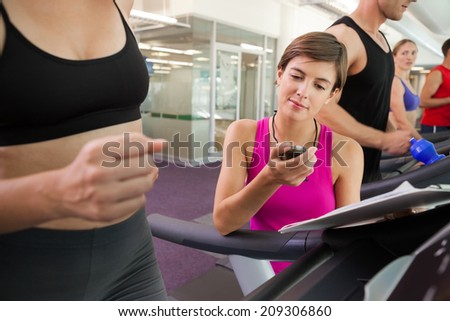 Trainer timing her client on the treadmill at the gym