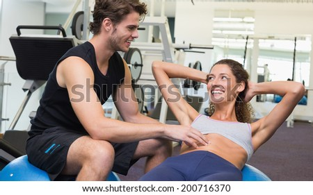 Trainer watching client do sit ups on exercise ball at the gym - stock photo