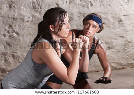 Trainer watching over young athlete exercising indoors - stock photo