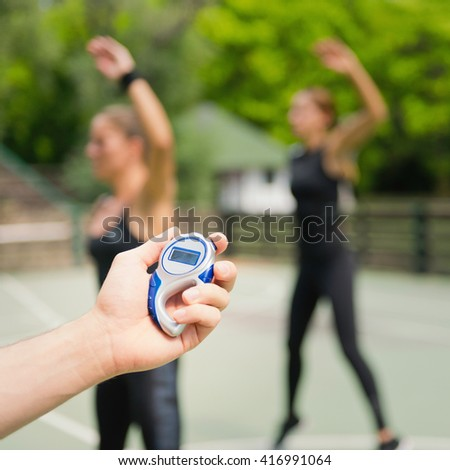 Trainer with stopwatch during outdoor exercise class - stock photo