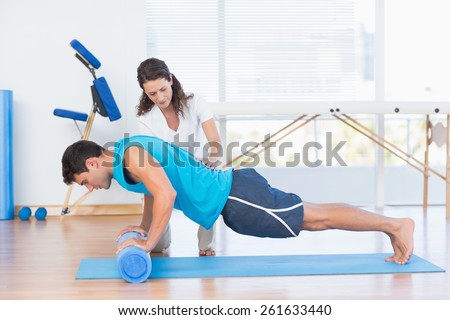 Trainer working with man on exercise mat in fitness studio - stock photo