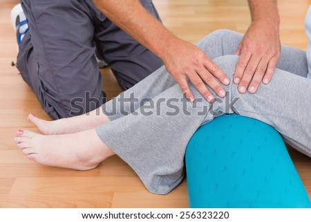 Trainer working with senior woman in fitness studio - stock photo