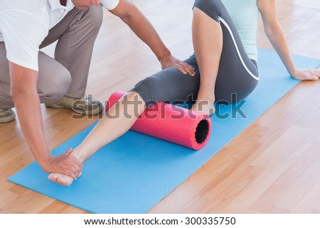 Trainer working with woman on exercise mat in fitness studio - stock photo