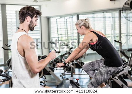 Trainer writing on clipboard and woman using exercise bike at the gym - stock photo