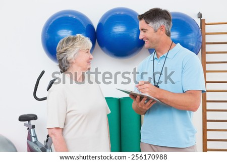 Trainer writing on clipboard with senior woman in fitness studio - stock photo