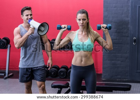 Trainer yelling through the megaphone while woman lifting dumbbells - stock photo