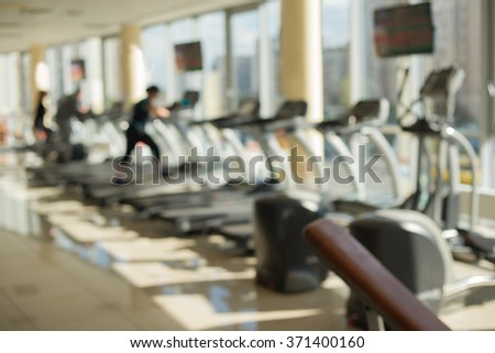 Training apparatus in gym. Blurred picture of gym. People are training on bikes and treadmills in gym. - stock photo