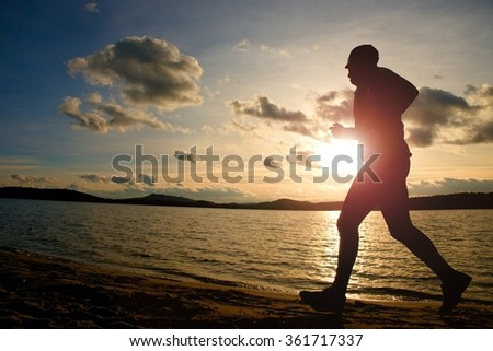 Training at sunset. A silhouette of jogger at path along lake coastline.