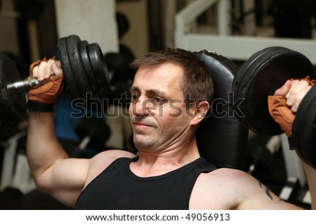 training dumbbells in gym. Male lifting weights for upper body strength building pecks, shoulders and biceps - stock photo