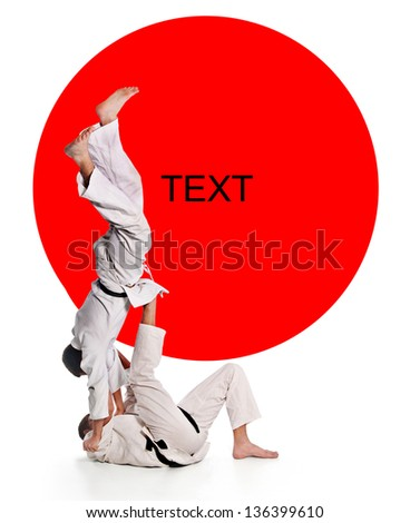 Training fight.two fighters on a background the Japanese flag.battle throw.Judo.figure in the karate.masters of hand-to-hand fight - stock photo