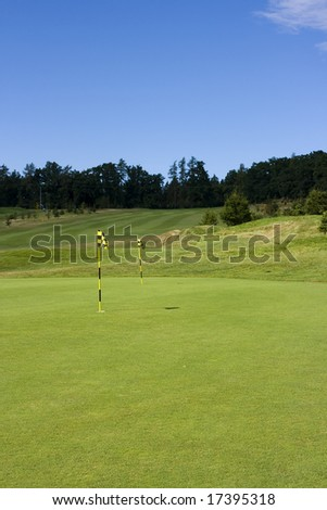 training green of a beautiful golf course with dramatic summer sky - stock photo