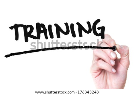Training hand writing with a black mark on a transparent board - stock photo