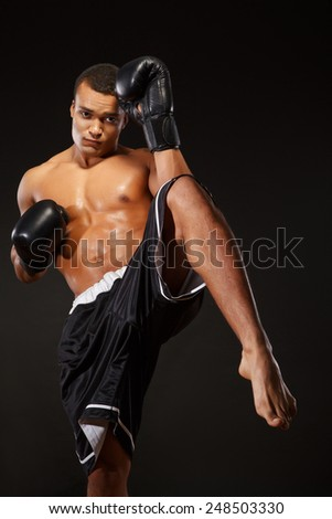 Training his kickboxing skills. Young shirtless African man in boxing gloves exercising kickboxing isolated against black background - stock photo