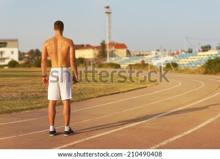 Training. Muscular athlete of the treadmill at the stadium - stock photo