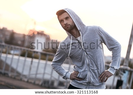 Training on fresh air. Handsome young man doing stretching exercises before running while standing outdoors - stock photo