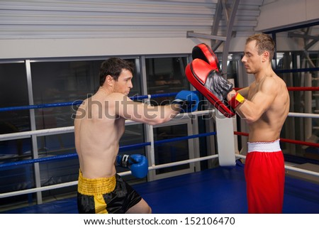 Training. Two confident men boxing on the ring - stock photo