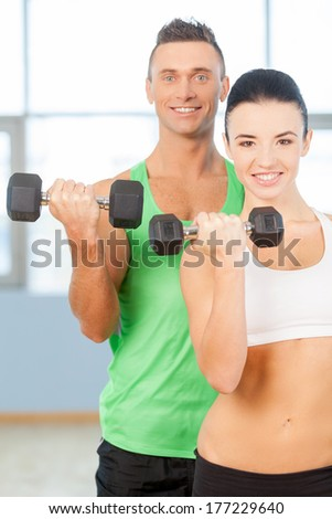 Training with dumbbells. Couple lifting dumbbells in a gym and smiling