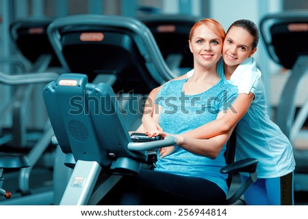Training with mom. Beautiful mature woman bonding her teenage daughter in sports clothing after workout on exercise bicycle in the gym - stock photo