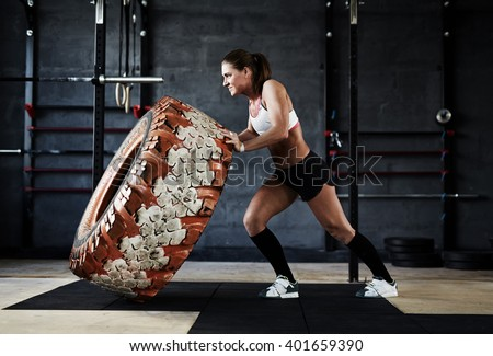 Training with tyre in gym - stock photo