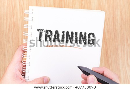 Training word on white ring binder notebook with hand holding pencil on wood table,Business concept. - stock photo