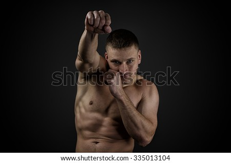 Training Young muscular boxer on a black background. Practiced punches before the fight. Hard light, dark lighting - stock photo