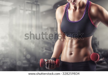 Training young sports woman in the gym with small weights - stock photo