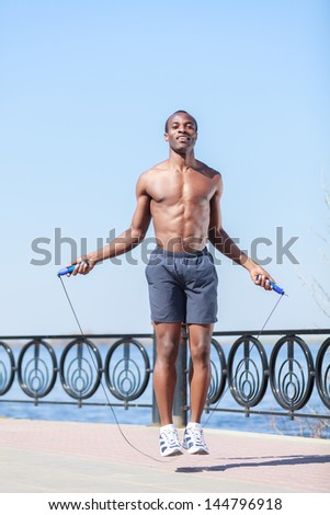 Trainings everyday. Young african descent men jumping on the rope - stock photo