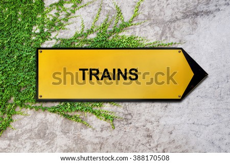 Trains on yellow sign hanging on ivy wall