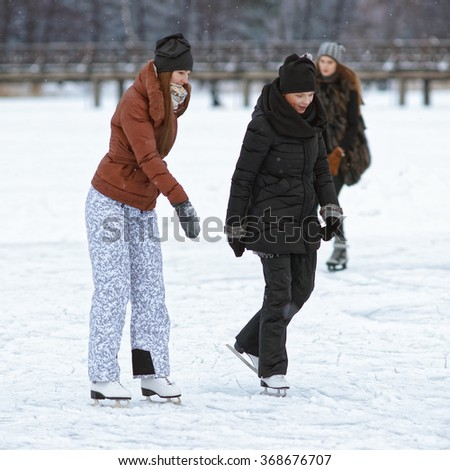 TRAKAI, LITHUANIA - JANUARY 7, 2016: Girl Friends Ice skating on rink in snow covered Trakai. Skating involves any activity which consists of traveling on ice using skates. Selective focus