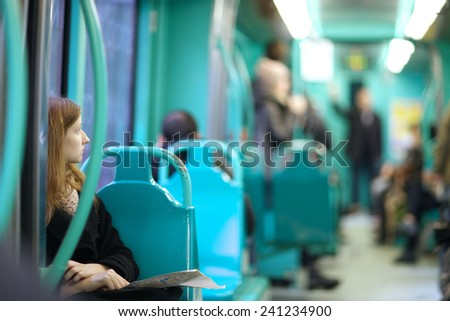 Tram interior, young woman looking aside to other passengers - stock photo