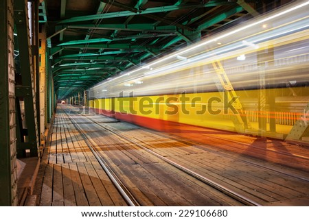 Tram light trail in the lower part of the steel truss Gdanski Bridge in Warsaw, Poland, vanishing point perspective. - stock photo