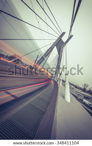 Tram lights trails on tram cable-stayed bridge in Krakow, Poland - vintage look